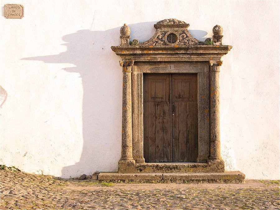 An old door with an ornate granite surround with setting sun casting a long shadow.