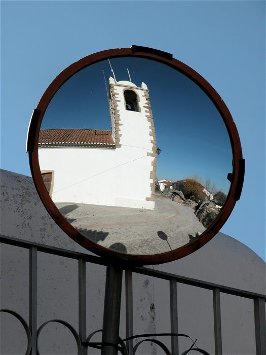 The tower of Igreja de Santiago, Marvao reflected in a circular traffic mirror